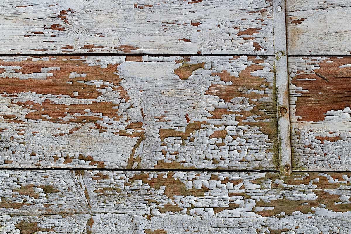 Verwitterter, ursprünglich weiß gestrichener Holzverschlag