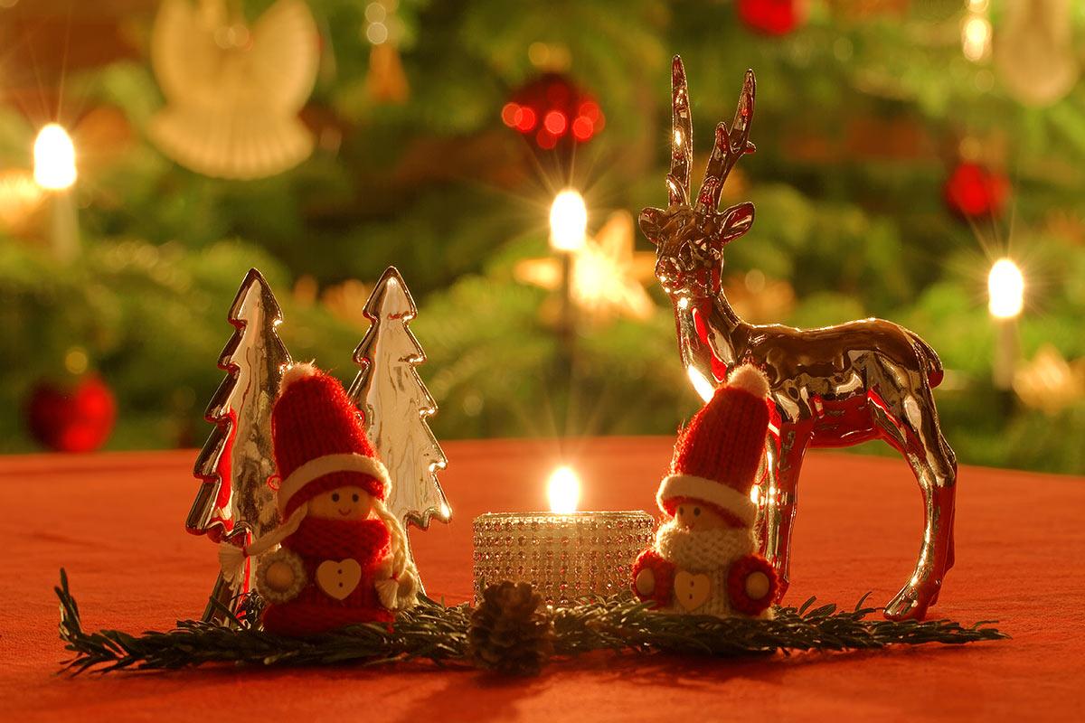 Weihnachtliche Dekoration vor erleuchtetem Weihnachtsbaum 2018