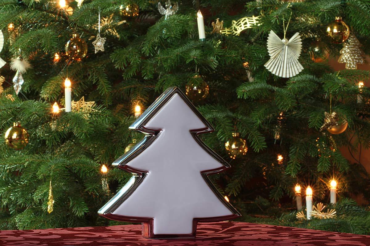 Weihnachtsbaumdekoration vor geschmücktem Weihnachtsbaum